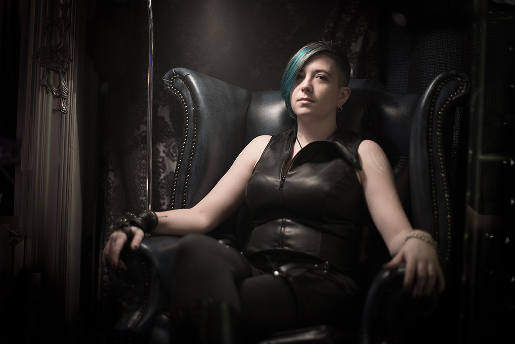 Sir Claire Black in all leather sitting waiting