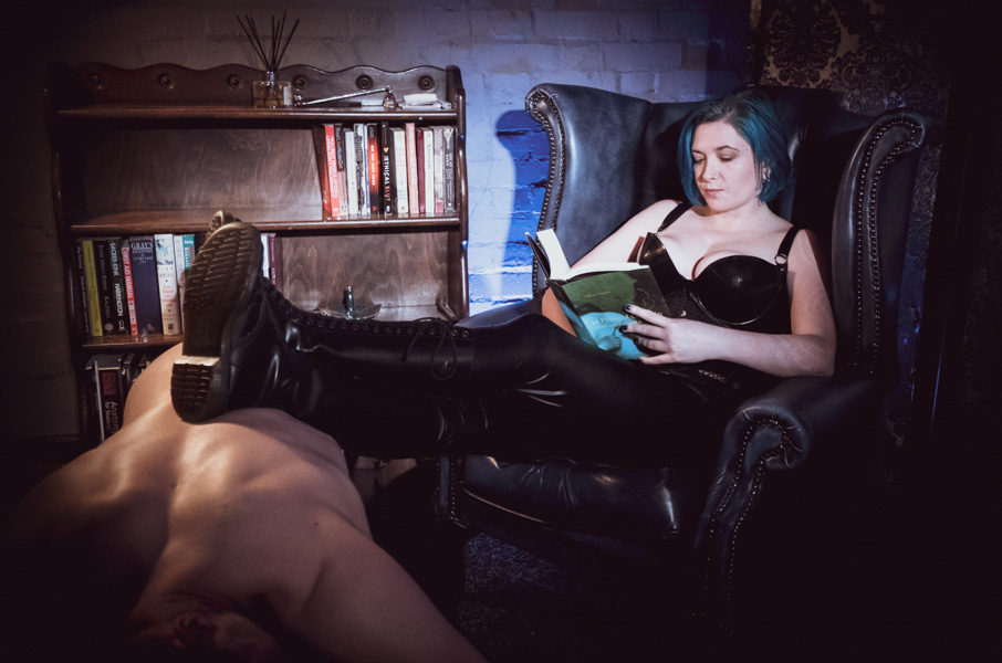 Latex Mistress in Dr Marten boots using human furniture