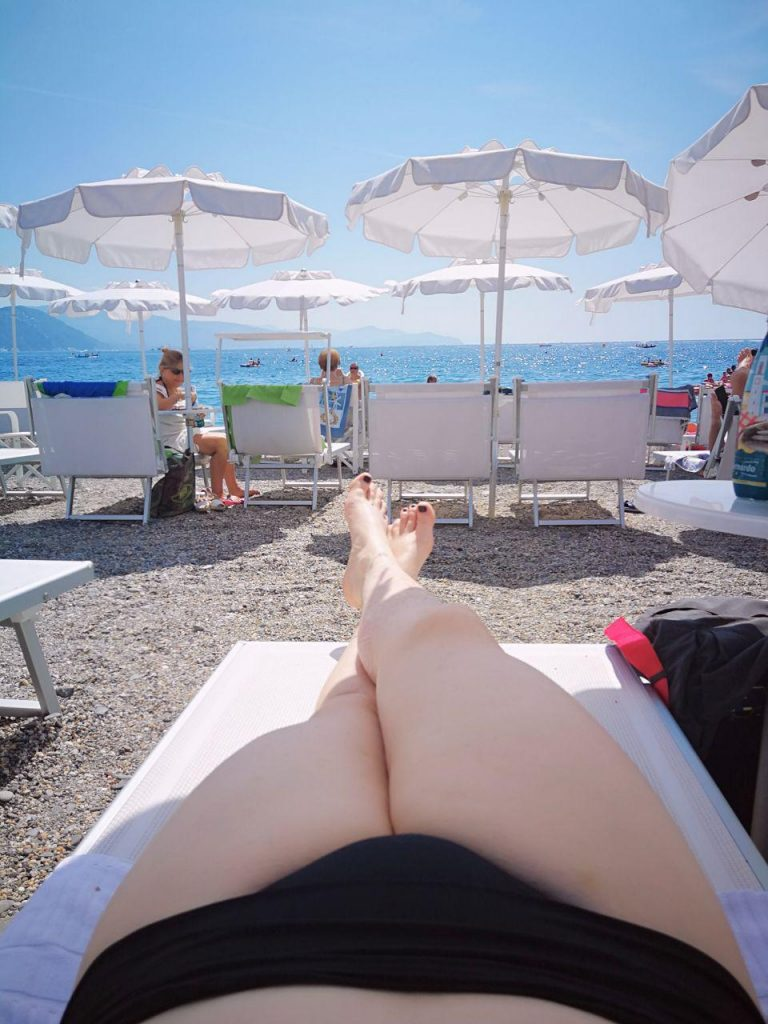 International travel companion Sir Claire Black in a bikini lying on the beach in Italy